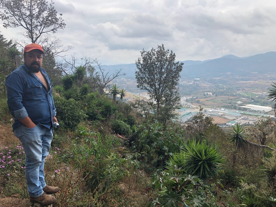 Alex Reynoso standing above the Escobal mine, pictured below. Location: La Cuchilla Aldea, one of the poorest areas in the region and one of the hardest hit by the mine. Tremors, noise, and environmental contamination have led to collapsed houses, shifting earth, and illness.
