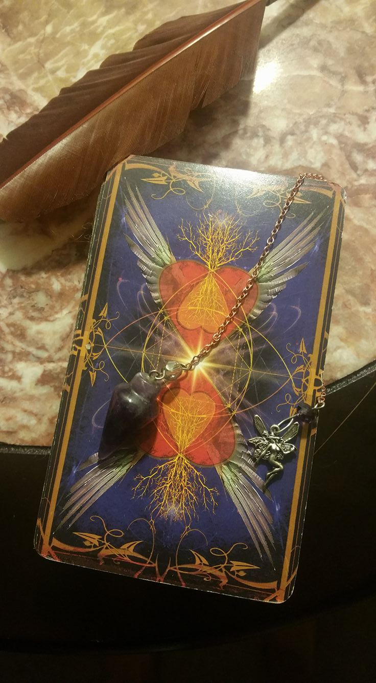 One of Tink's Tarot card decks and her beloved amethyst pendulum.
