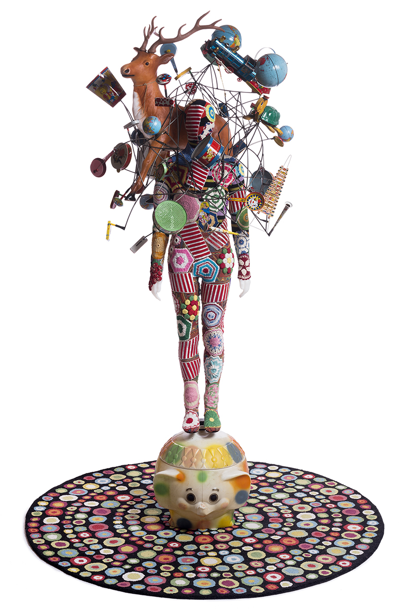 "Nick Cave,  Soundsuit , 2015, mixed media including vintage toys and globes, wire, fabric, rug, metal and mannequin, Soundsuit: 117 (H) x 50"" (W), Rug: 85"" diameter, Inventory #NC15.007 ©Nick Cave.  Photo by James Prinz Photography.  Courtesy of the artist and Jack Shainman Gallery, New York."