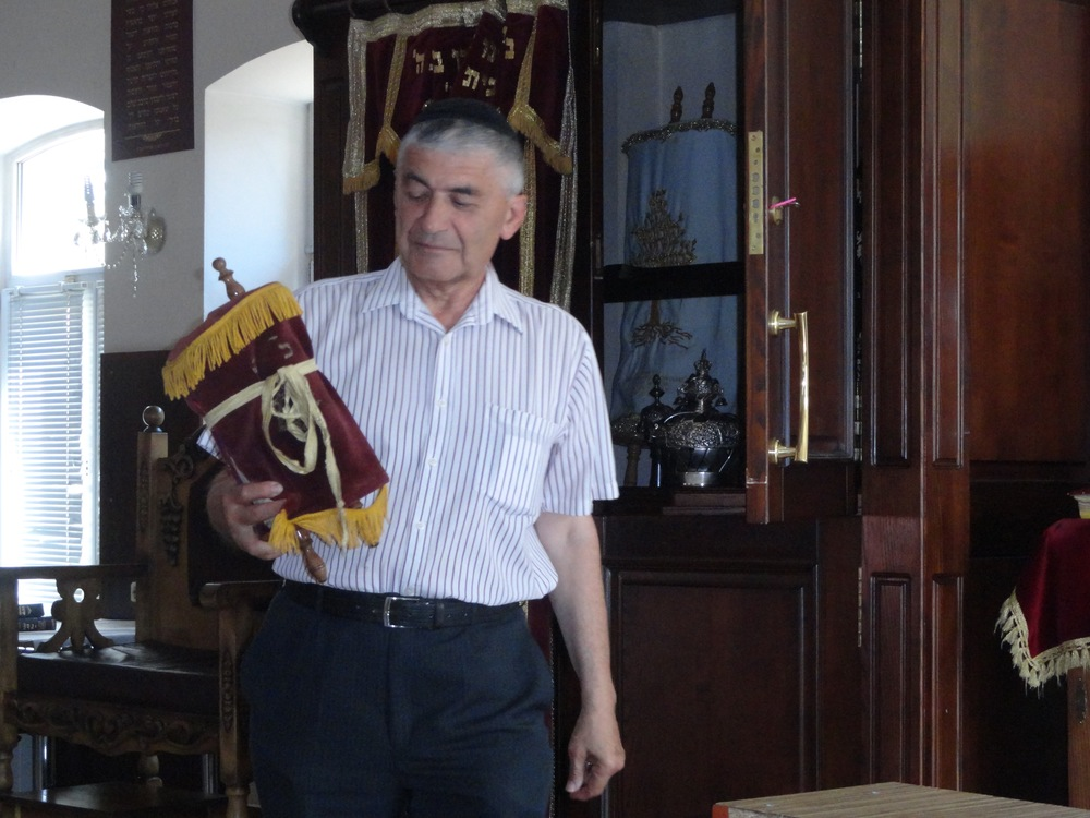 Joseph Liberman holding a torah that survived the Holocaust in Pinsk, Belarus.