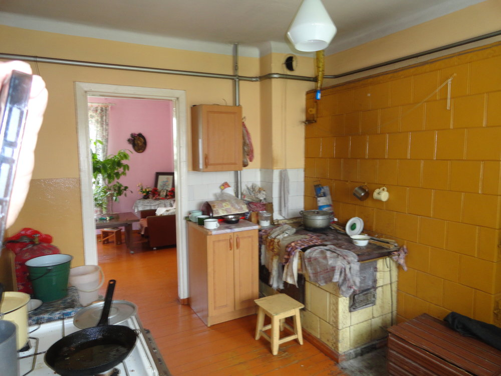 Pranè's kitchen -- she has a modern gas stove so she uses the old wood fired stove as a counter.