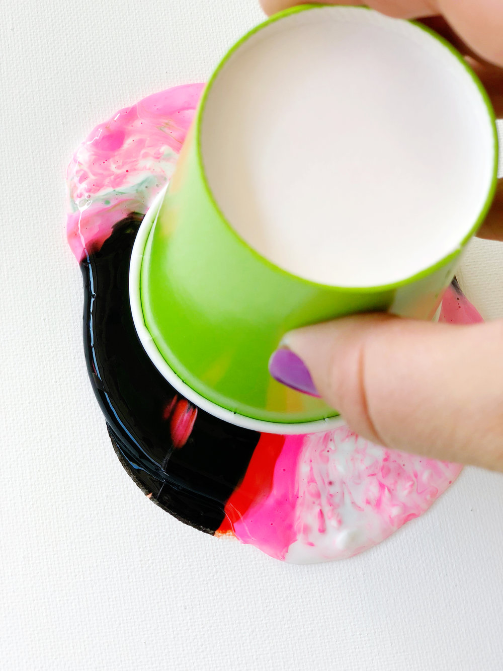 11. Next, slowly pick up the cup and very quickly release some of the paint onto the painting surface. Then place the cup back down tightly.