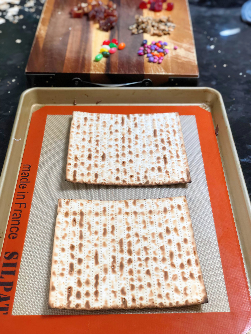 1. Place two pieces of matzah onto a sil pat (or parchment paper) lined sheet pan.