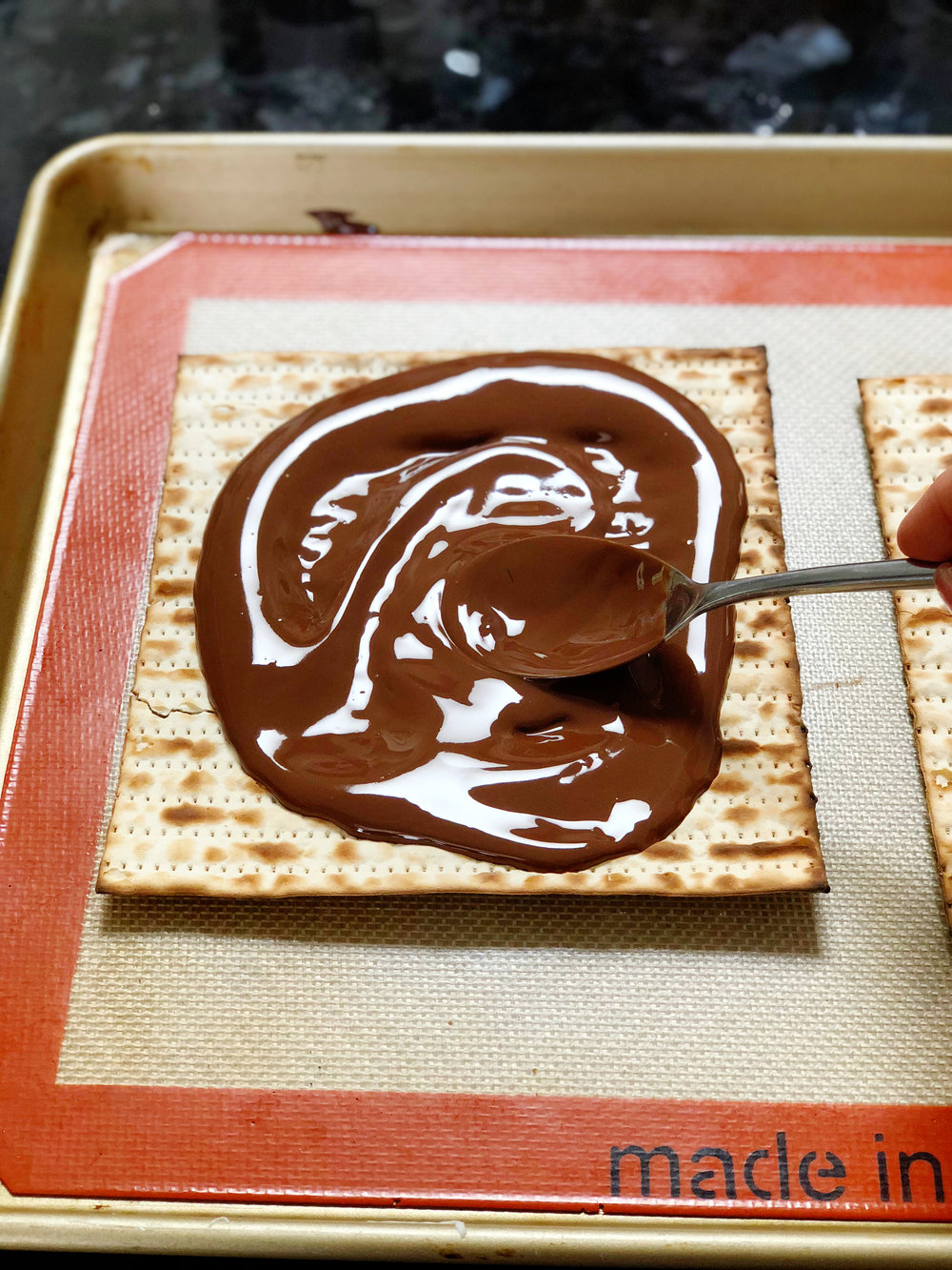 5. Now, pour half the chocolate mix over each matzah and spread around in an even layer with a spoon or spatula.