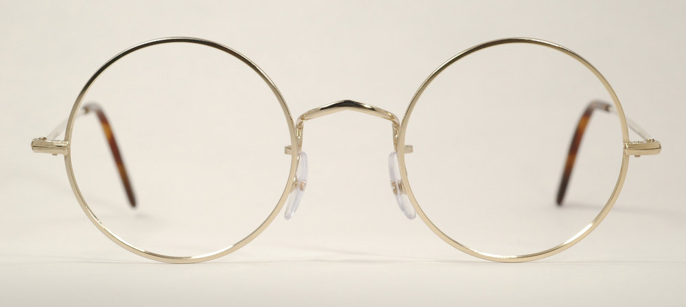"From the information article: "" It looked as if somebody fastened electronics to every inch of a pair of wire-framed glasses"".  Start with the wire frame and imagine some circuit boards.  Hopefully, the bulk added from that will be small enough that they still look reasonable."