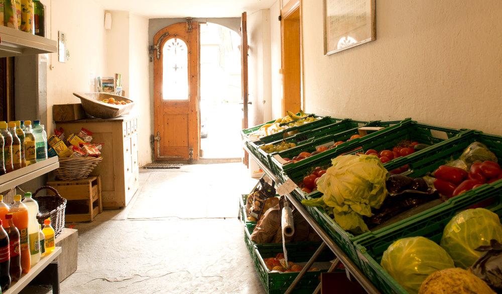 Der Blick durch den Gang des Ladens Richtung Eingang. Frisches Obst und Gemüse,einige Erfrischungsgetränke, Knabbergebäck und Postkarten sind hier zu finden. Links geht es in den Hauptraum mit Kassa, der dann weiter in den Käsekeller führt. Rechts geht ein Eingang in den Weinkeller.