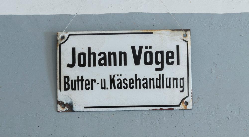 Ein altes Schild aus den Anfangsjahren des Käsladens. Es ist schon ein bisschen rostig an den Ecken. Darauf steht: Johann Vögel – Butter- u. Käsehandlung.