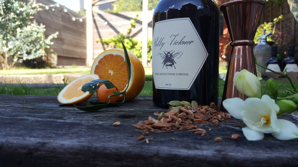 A bottle of Nelly Tickner tonic cordial, shown with some oranges, various botanicals and a copper jigger