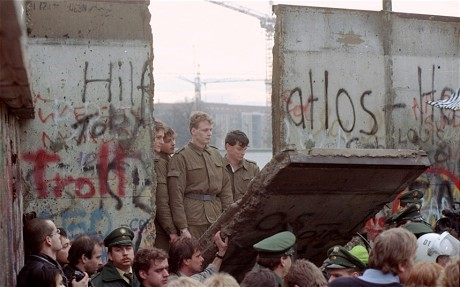 Demonstrators pull down a segment of the Berlin wall at Brandenburg gate in 1989