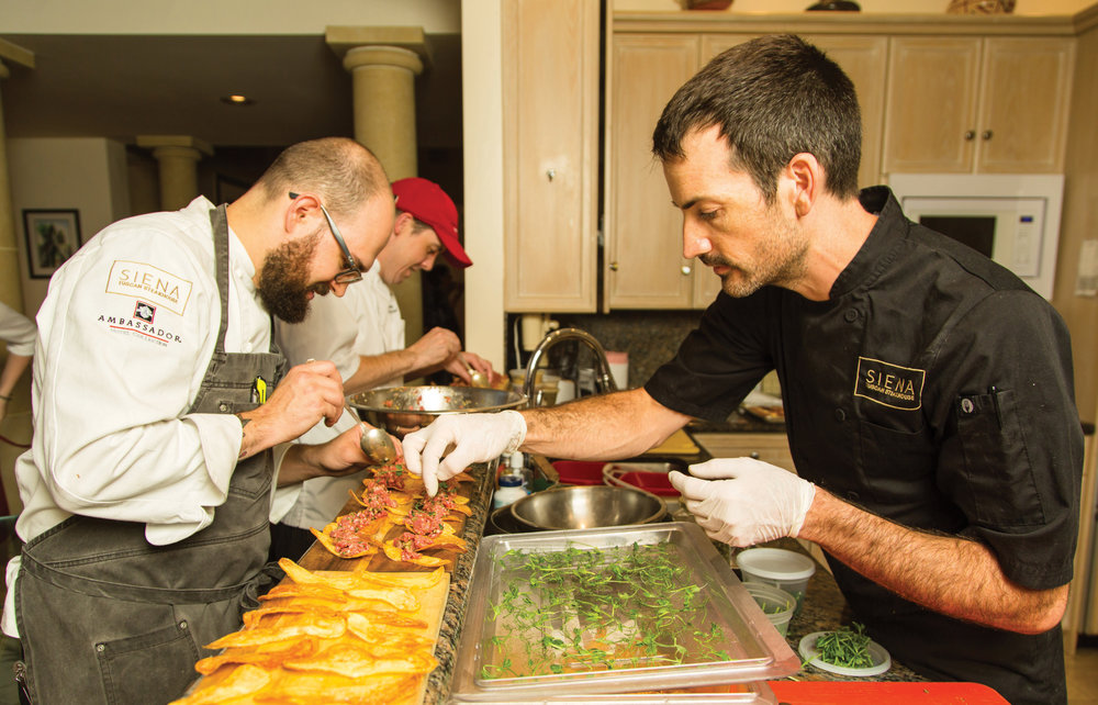 Josh Rathbun, front left, executive chef at The Ambassador Hotel and its Sienna Tuscan Steakhouse, prepared a memorable seven-course feast for 30 lucky diners at the east-side home of Laura and Phil Knight.