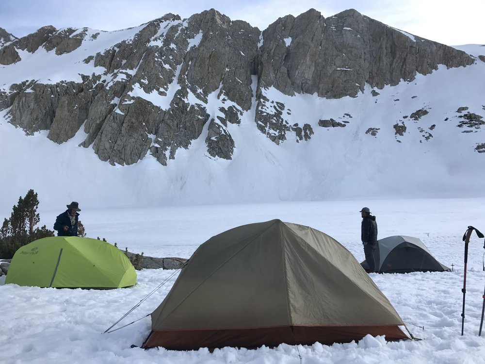 Camping on snow in front of a frozen lake. We punched a hole in the lake with our whippets to access water, and were feeling ambitious that day, so we trampled little sidewalk paths between our tents!