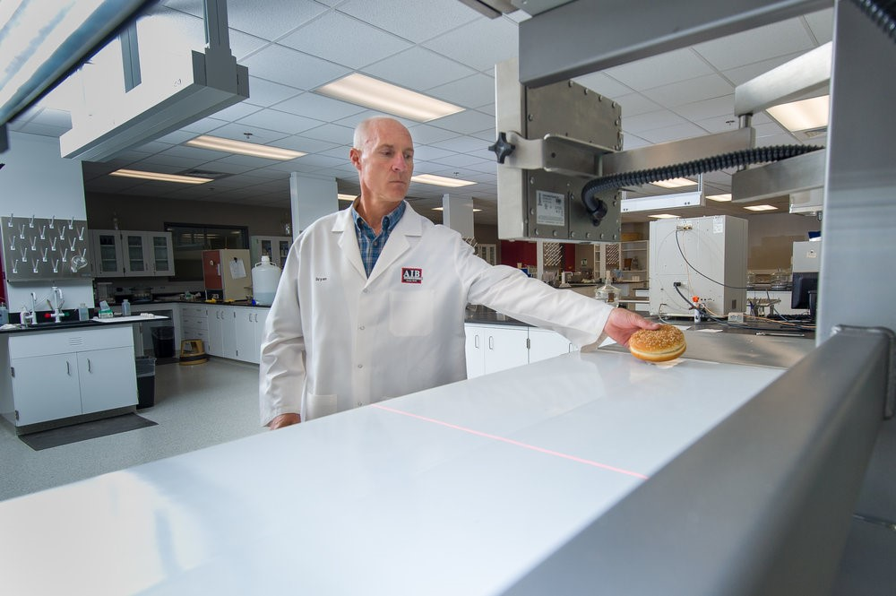 Glaser coloca un pan de hamburguesa en la cinta transportadora del sistema de imagen de producto.