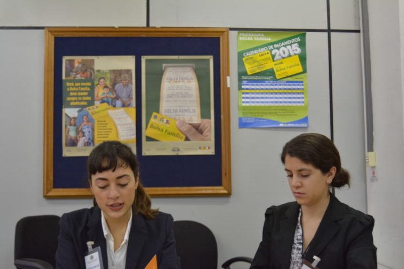 Nicoli DosSantos (research, left) and Nina DaNobrega Garcia (research, right) accompanied by Bolsa Familia cash withdrawal posters and payment calendar in the background (Photo Credit: A Sim)