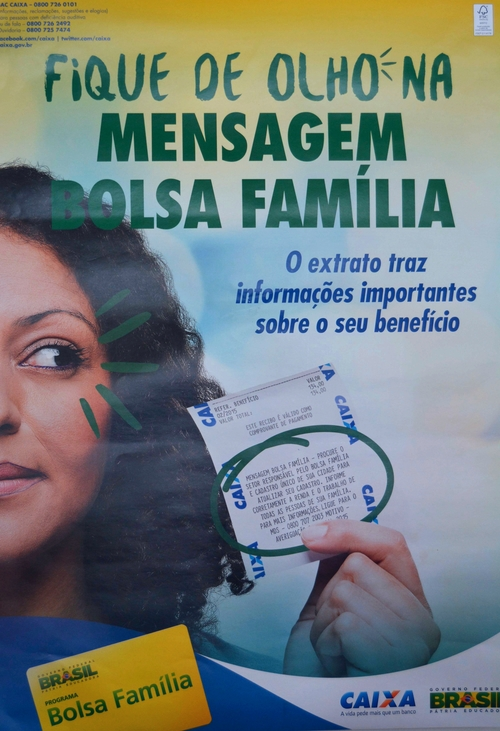 "A poster describing Bolsa Familia messages for beneficiaries: ""When you go to withdraw, get important information about your benefits.""   (Photo Credit: A Sim)"