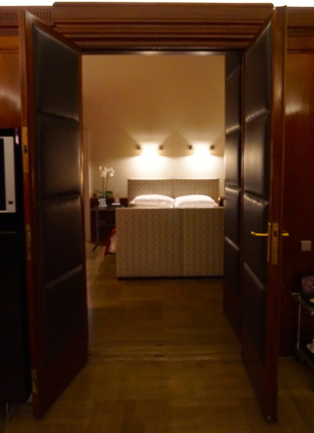 Die gepolsterten Türen sind original erhalten und trennen den Schlafraum vom Wohnraum. Die  bauzeitlichen Türen mit Lederbezug sowie der Parkettfußboden verströmen ein wunderbares Flair.