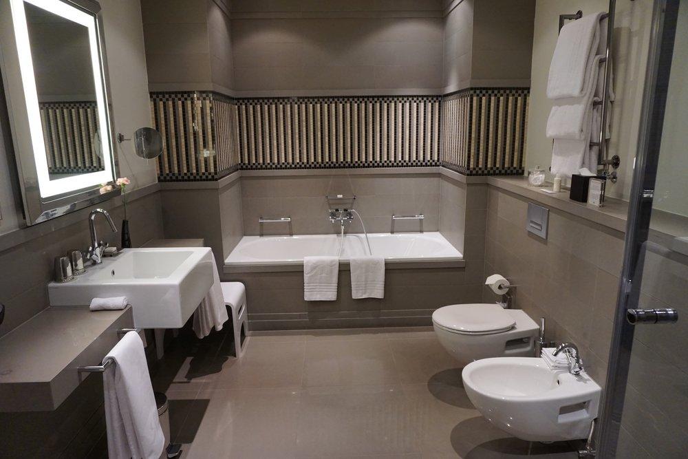 Die großen Marmorbadezimmer sind mit Mosaiken dekoriert und verfügen über eine Badewanne sowie eine separate Dusche mit Sitzgelegenheit. Auch sehr positiv, da ich immer friere: die Fußbodenheizung. Der Spiegel wurde mit viel Sorgfalt und Liebe ausgewählt. Selten habe ich so gut und frisch in einem Hotelbadezimmer ausgesehen. Das Licht kommt von vorne. Ganz einfach, wird aber in anderen Häusern selten so umgesetzt. Perfekt für BeFiftys, vor allem nach langen Berlin-Nächten.