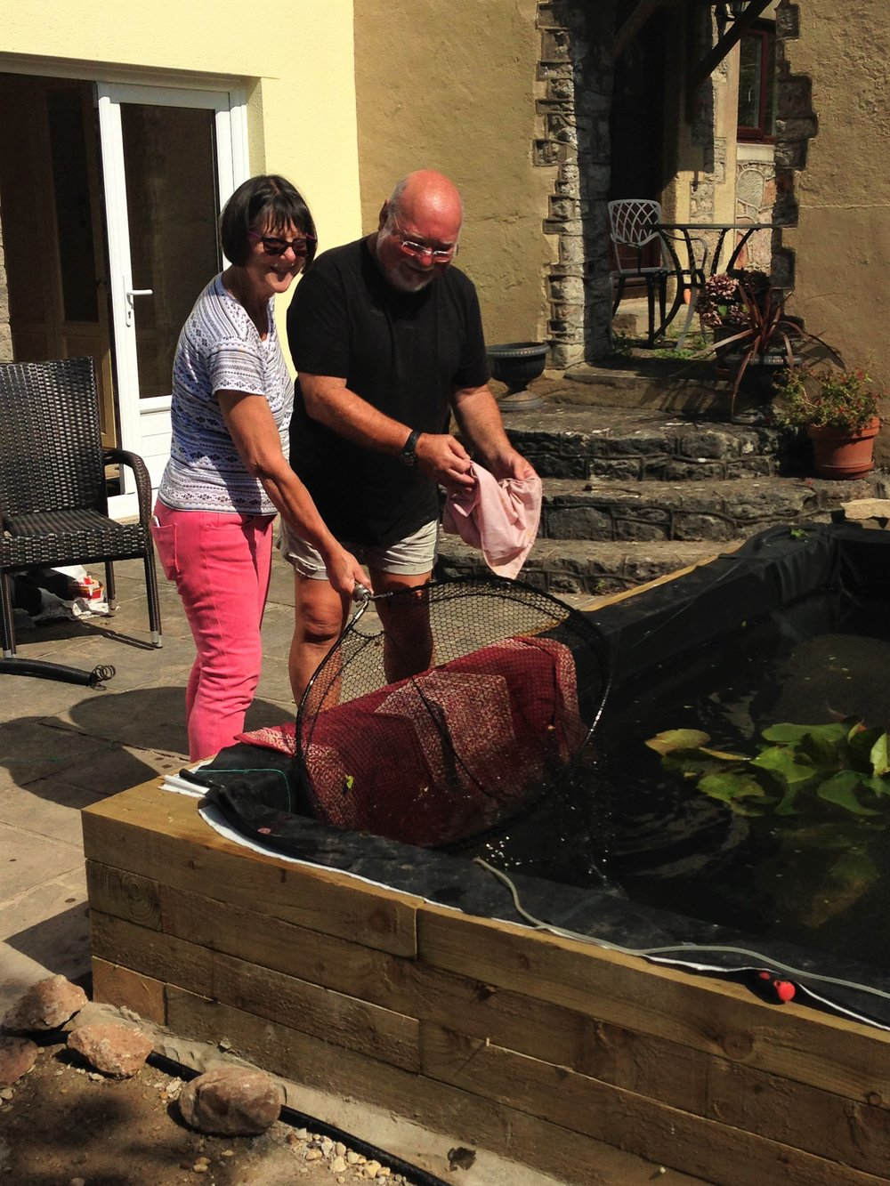 Two happy clients introducing their Koi into the new pond with well water and an already matured filtration system!
