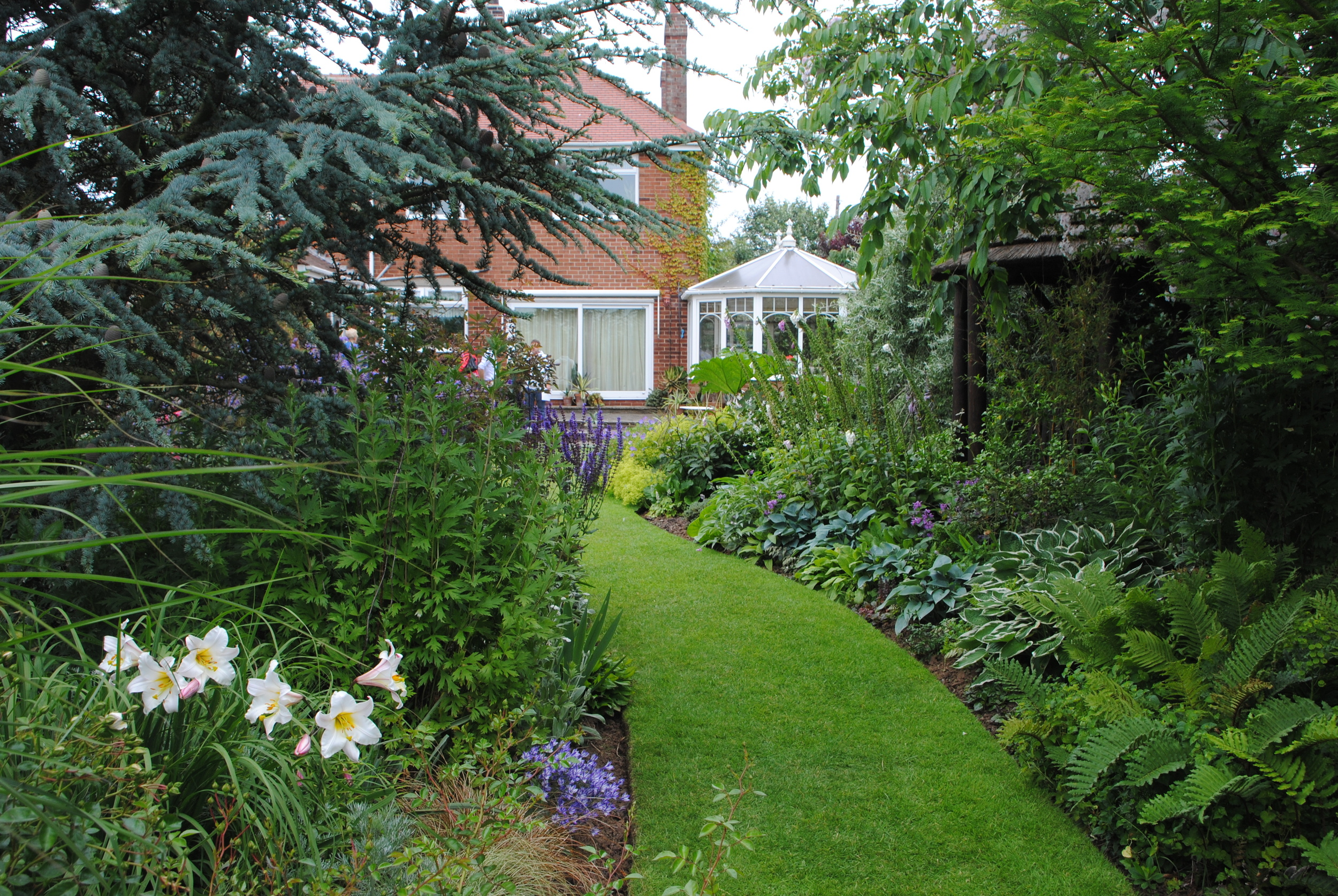 Lush borders and winding paths make the garden seem much larger than its actual size.