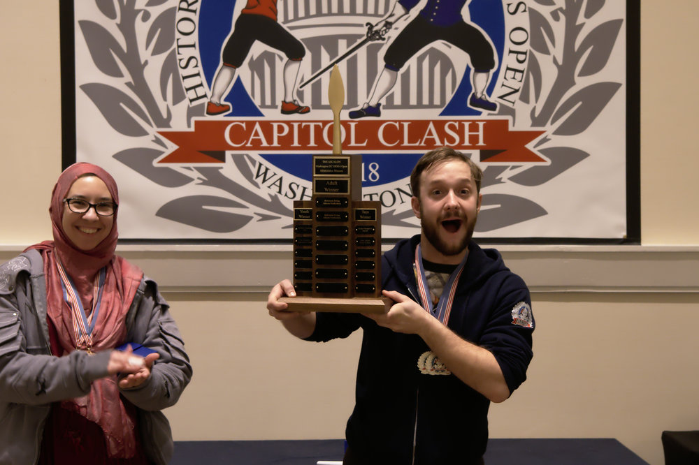 The top three winners of the HEMAthlon of the adult category in 2016. BRONZE: Doug Bahnick (right), Virginia Academy of Fencing; SILVER: Tim Kaufman (left), New York Historical Fencing Association; GOLD: Mackenzie Ewing (center, holding the coveted ASCALON trophy), Atlanta Freifechter Guild.