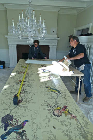 """Birds & Bees,"" the wallpaper that the owner selected from the vendor Timorous Beasties, is rolled out for installation by Robert Montagnese of Wallpapers Unlimited, to enliven the formal Dining Room with full-size birds and bees."
