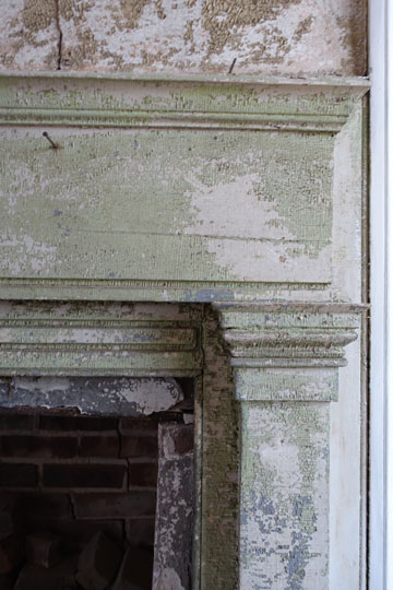 A detail of the fireplace mantel shows the alligatoring of the paint finish, soon to be restored.
