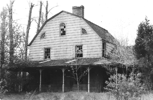 The south side of Holman house in 1962, showing a wrap around porch with Queen Anne style posts.  The porch no longer exists. Photo from Preservation Long Island's archive.