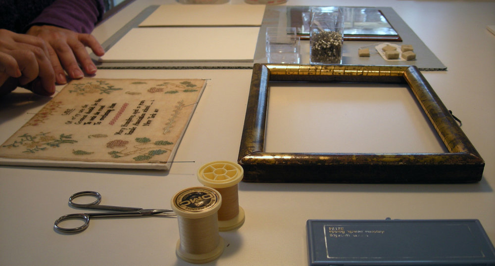 A sampler being hand-stitched to a fabric covered ragboard in preparation for framing.