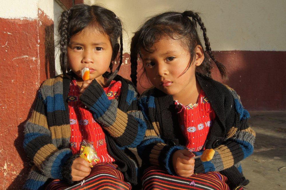 Two beautiful young Guatemalan girls enjoying a lollipop.