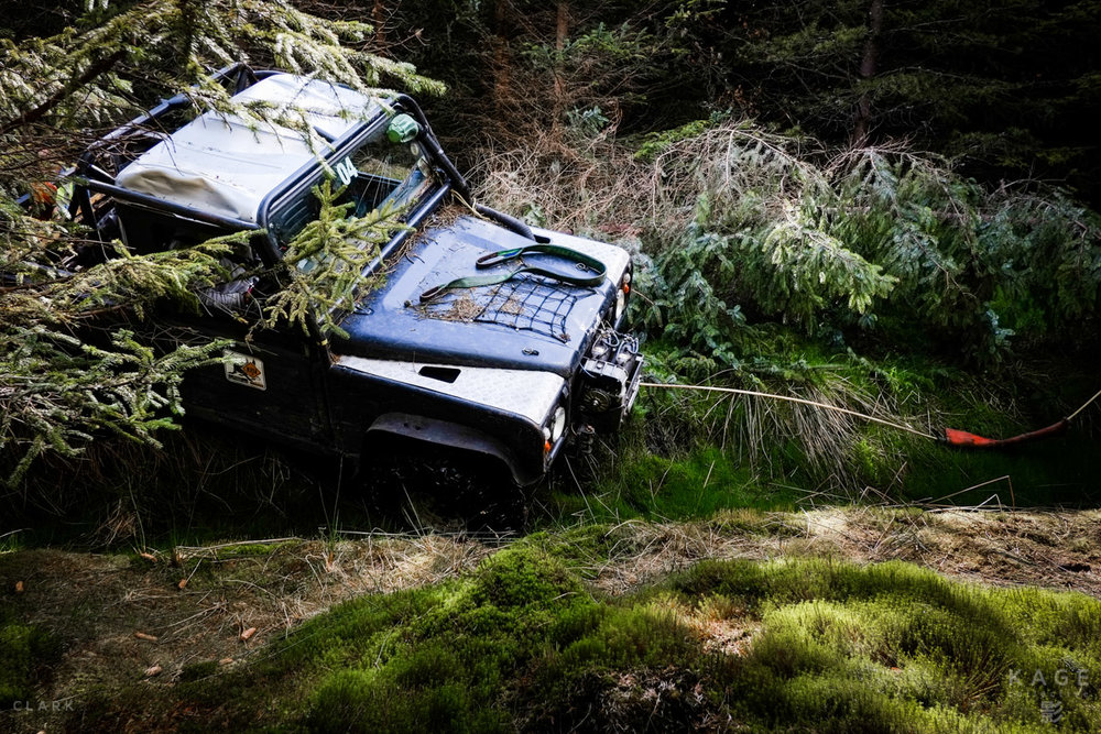 A driver waits patiently as his co-driver attaches their Land Rover's winch to a tree in an attempt to pull them out of a ditch.