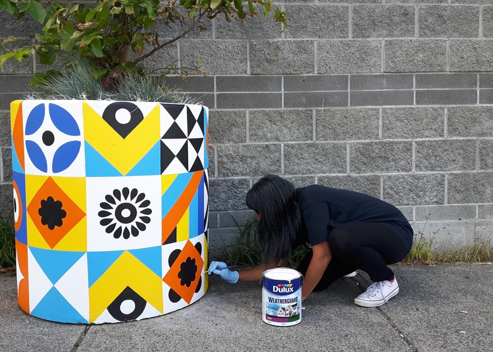 Sandeep Johal painting a giant concrete planter in front of the Uncommon Cafe for the Strathcona BIA X Hastings Urban Tree Nursery