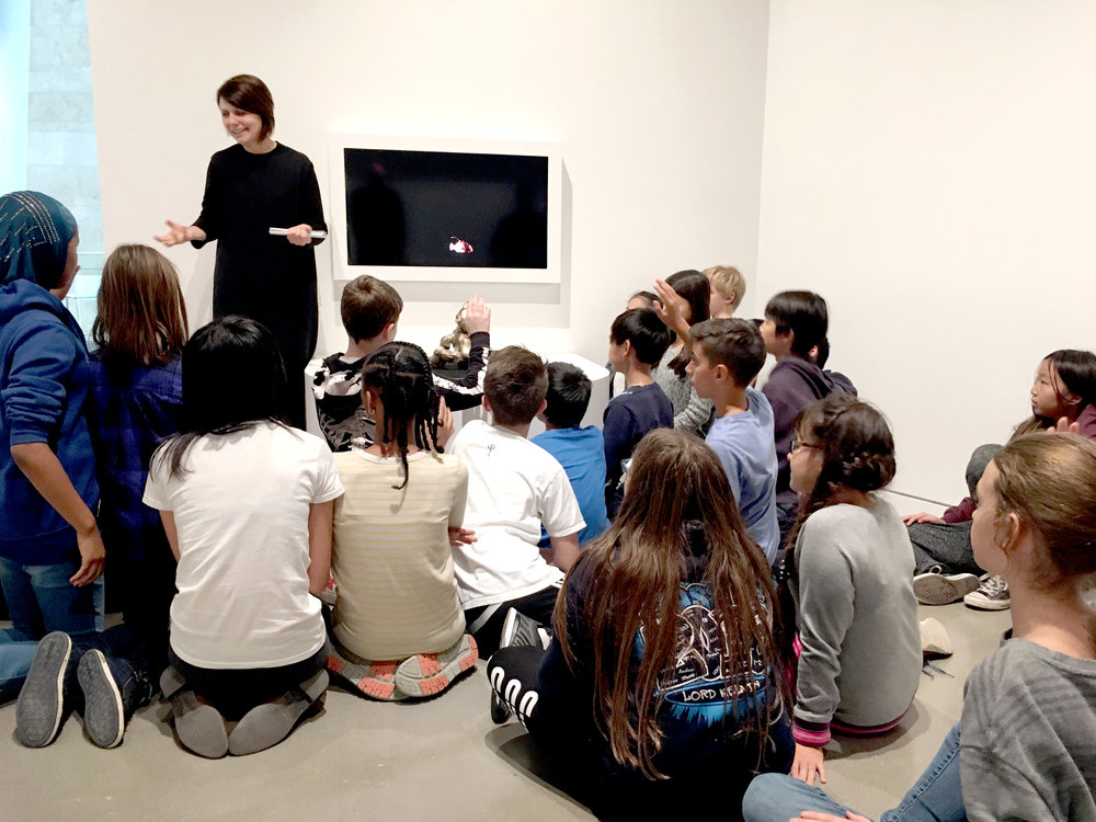 Sarah Speaking to a group of gallery visitors about the November 2016 exhibition at the New Media Gallery titled WITNESS. They are sitting in front of a work by France Cadet entitled Do Robotic Cats Dream of Electric Fish?
