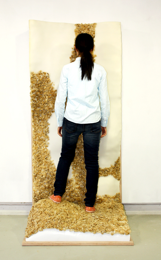 landscape portrait, 2014   foam, cigarettes, oak  Over 1,200 cigarette butts blended into a soft material for an interactive landscape allowing the viewer to explore the unrecognizable material. The rolling landscape hints to the eVER-GROWING pollution, which is altering the environment.                                                                                                                                       private collection