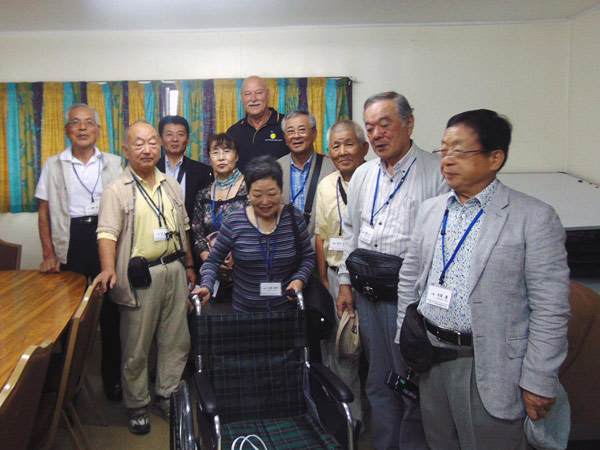 ANGAU CEO (background) and the Tour Group with the wheelchair.