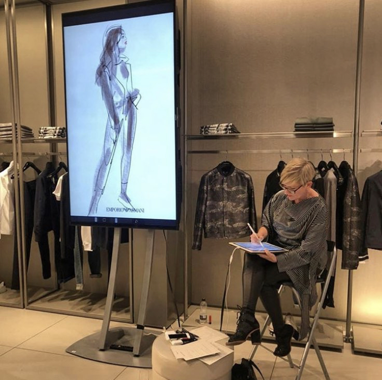 Jacqueline sketching at a live event at The Mailbox, Birmingham.   iPad Pro connected to 2 metre monitor for Emporio Armani.   Art work was printed on location and presented to each customer in a frame