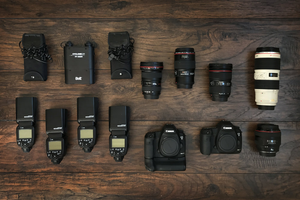 This is the basic equipment I bring to your wedding. I use professional-grade Canon equipment matched with fast glass including: Canon 5D Mark III bodies, a 100mm f/2.8 macro, a 24-70mm f/2.8 zoom, an 16-35 f/2.8 wide-angle, a 70-200mm f/2.8 telephoto, an 85mm f/1.2 portrait lens; and Canon 600EX-RT flashes powered by Bolt battery packs. Not shown: MagMod lighting modification system.