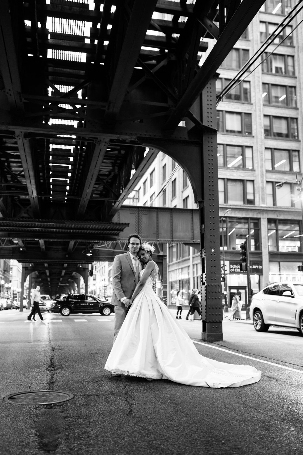 Portrait of bride and groom under L train tracks in Chicago
