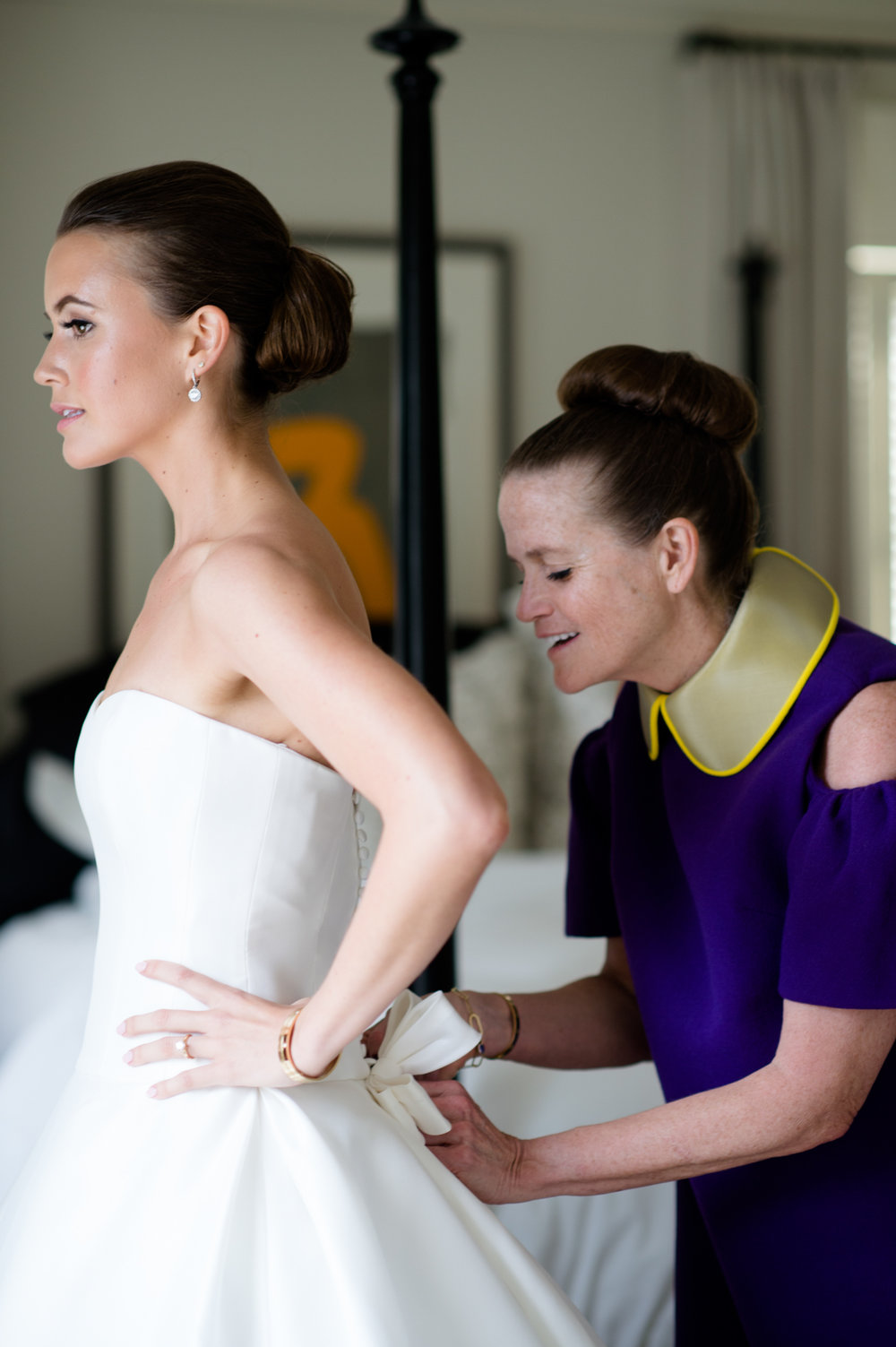 Mother of the bride helps bride dress for wedding in Chcarleston, South Carolina