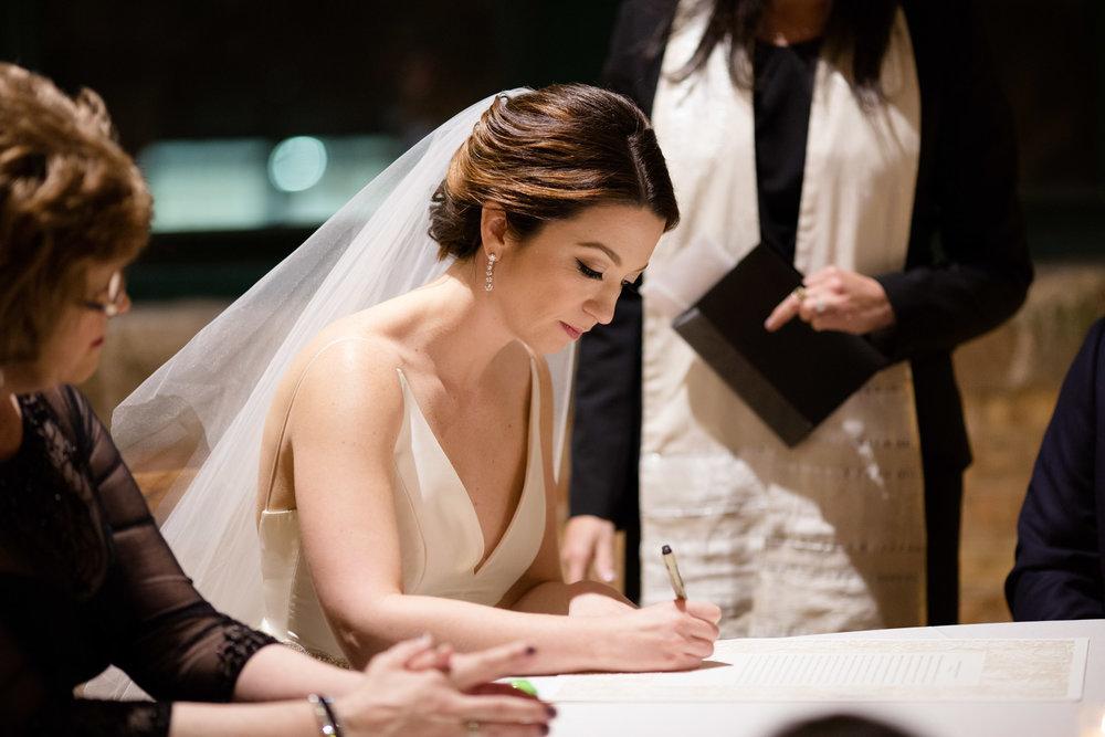 Bride signs ketubah at Bridgeport Art Center wedding in Chicago