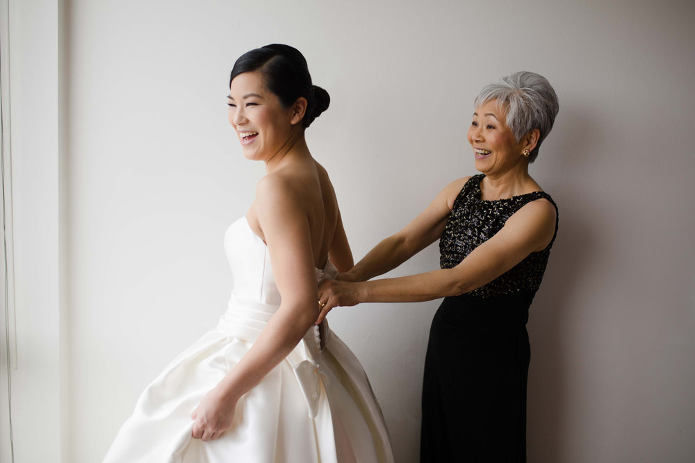 Bride's mother helps her get ready for Art Institute of Chicago wedding.