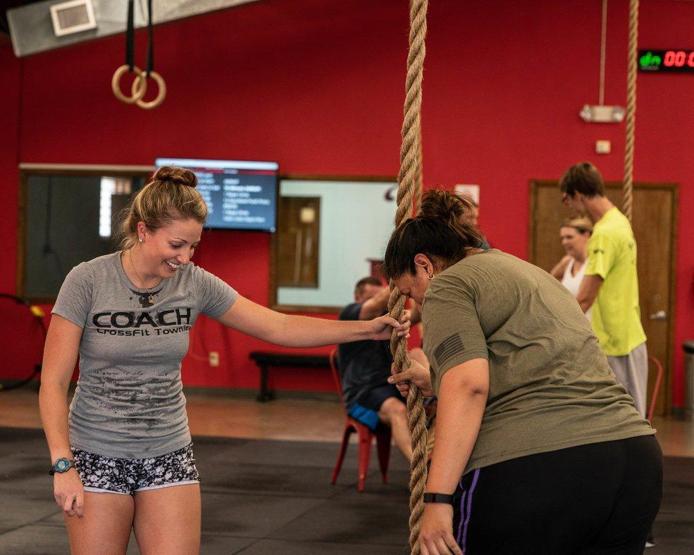 Coach Kelly Ledger shows Martha Millard how to do a rope climb
