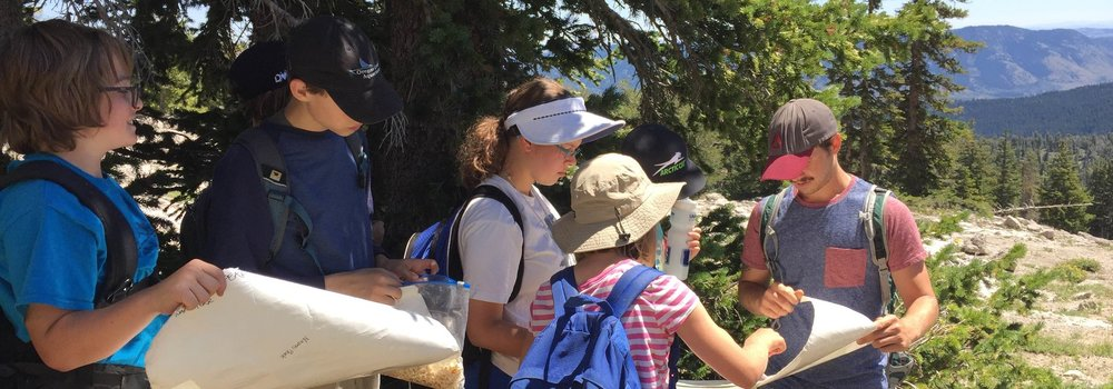 SNC Camp staff teaching campers how to read topographic maps on a nature hike in Logan Canyon.