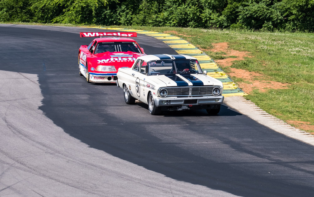 A 1964 Falcon about to get passed by a much faster Mustang. But the Falcon - driven with great entertainment, won its class.