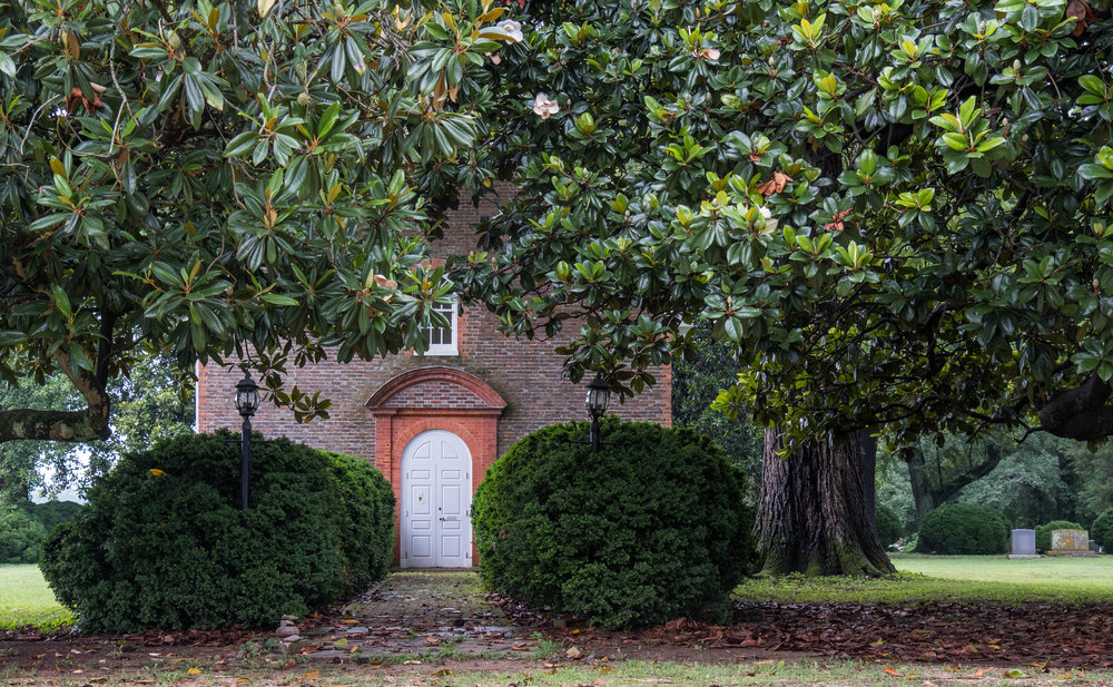 The entrance is almost hidden behind the towering Magnolia trees.