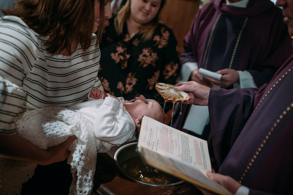 newborn baby gets baptized at notre dame