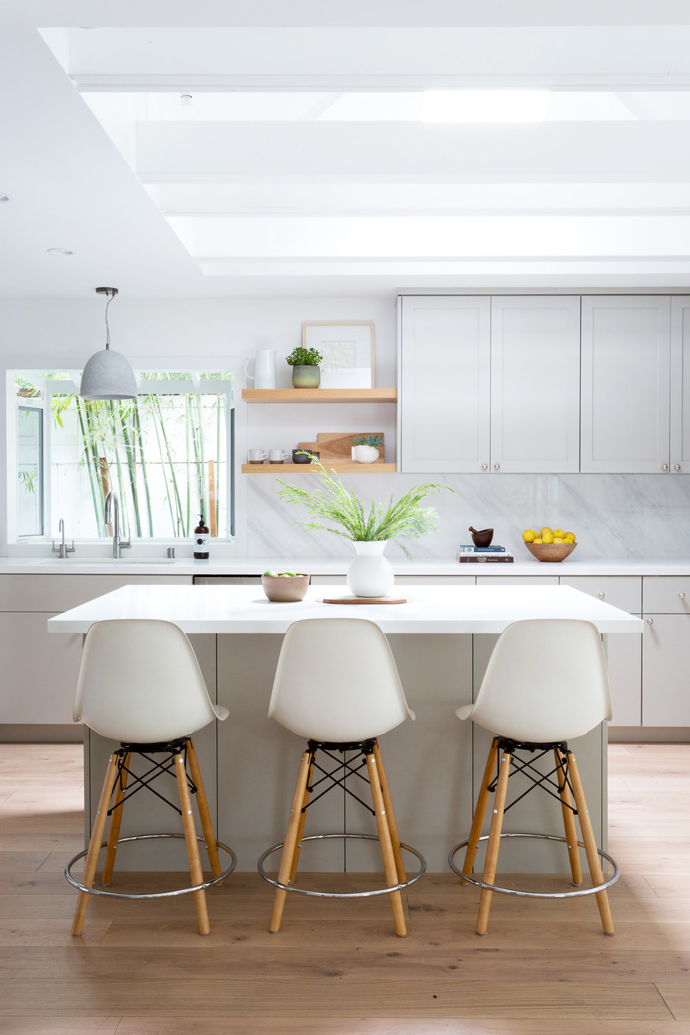 Light grey modern kitchen with white barstools designed by Carly Waters Style