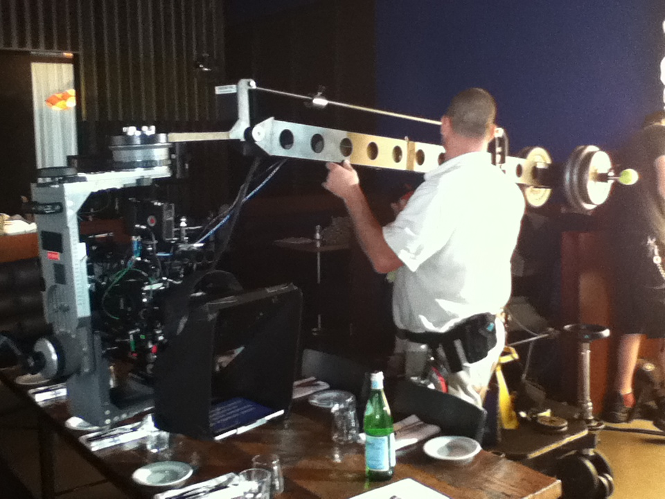 "This shot shows a unique configuration myself and my great team devised for a shoot for San Pellegrino. Camera is on two pieces of track, on a G-jib, underslung lambda head, with a 10"" teleprompter and a clip-on mattebox (with shade removed), to afford us the ability to use two 4 x 5.65 filters . Remote focus was employed as well.  Camera was a Red Epic and lenses red pro primes."