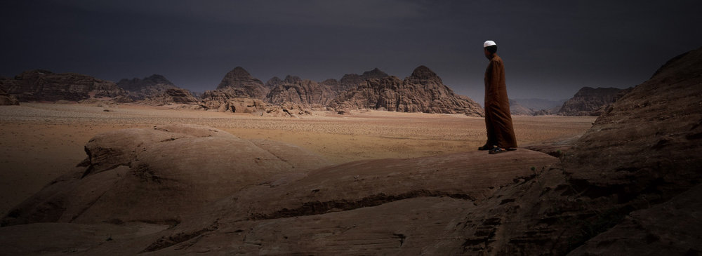 Raad standing in the desert.   Our guide through Wadi Rum desert stands in for a picture for me.   This shot taken on an XPAN II (one of my favourites, and I still use it today) with 100 ISO Fuji Reala (sure hope they don't stop making this). Taken on a tripod, as I had Raad move about in the landscape for a composited , ghosted print later on. This shot shows heavy grad effects applied & is printed down.