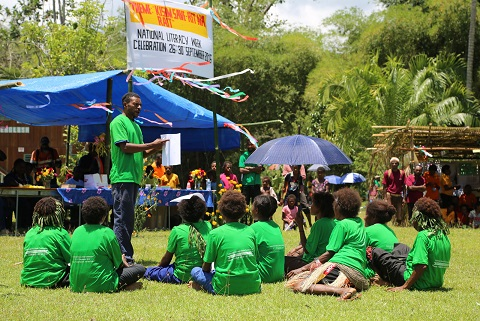 Adult literacy and numeracy students (above and below) perform activities at Zindaga Primary School grounds.