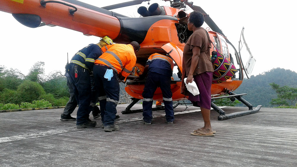 The Wafi-Golpu project team assisting with the medivac of Lupito to the Manolos Helicopter at the Wafi camp helipad.
