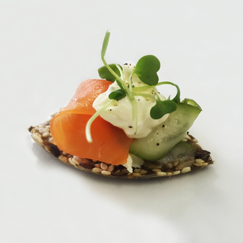 salmon trout on seeded cracker with pickled cucumber cream cheese and watercress